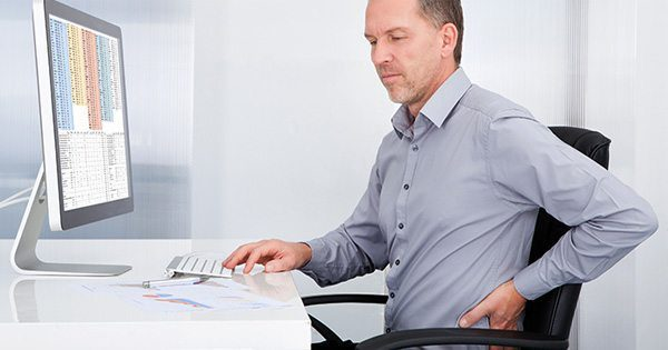 blog picture of man sitting at desk grabbing his back