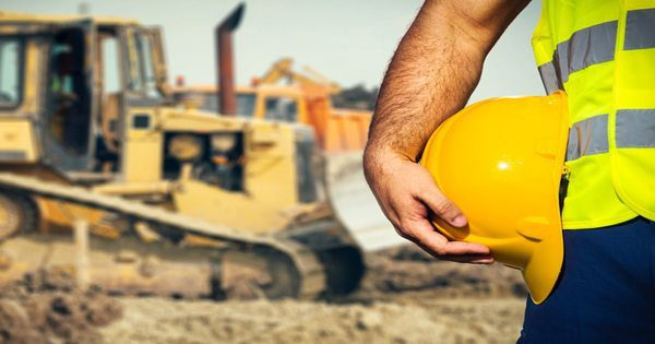 blog picture of construction site background worker's hand holding his hard hat