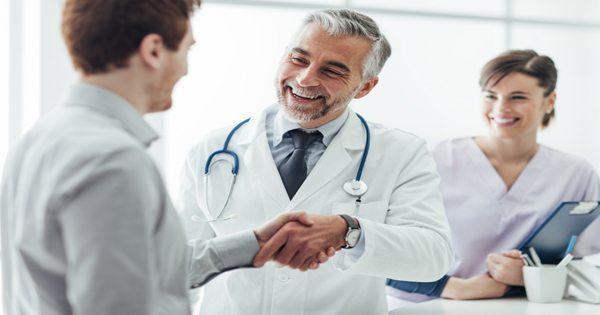 Foto blog dokter menggoyang pasien dengan perawat atau asisten di latar belakang