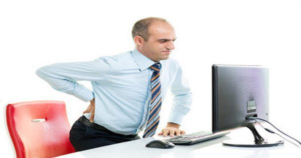 blog picture of man at office desk with sciatica pain