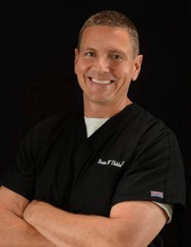 blog picture of chiropractor smiling arms crossed