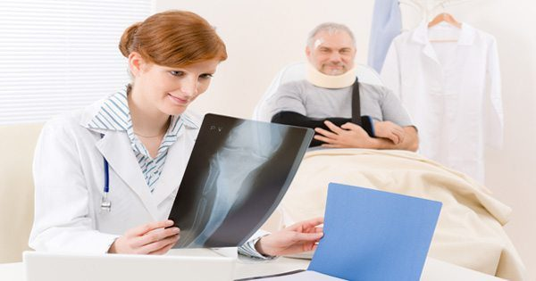 blog picture of doctor looking at x ray of patient sitting in the background