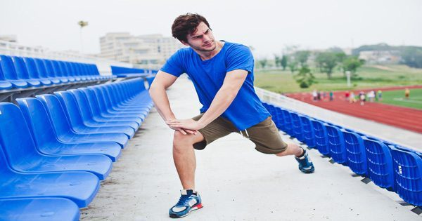 blog picture of runner stretching leg out in stadium seats