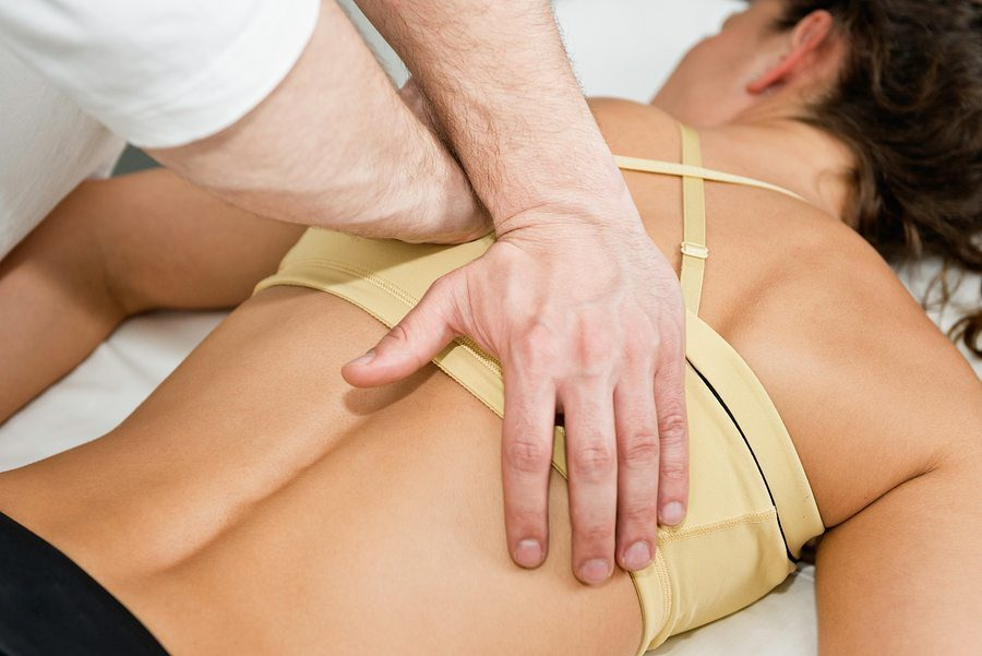 blog picture of lady lying down with hands of chiropractor doing adjusting on back