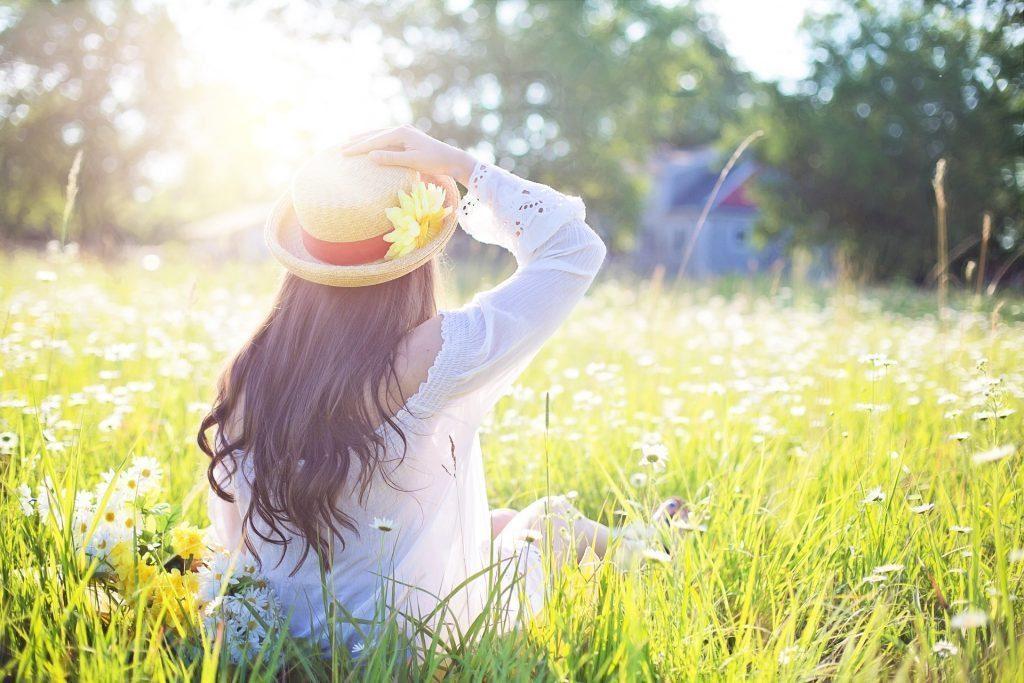 太陽が輝いて花のフィールドに座っている女性のブログ写真