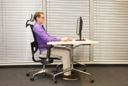 blog picture of young man sitting at desk with ergonomic chair and proper posture