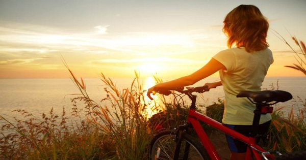 blog picture of a lady walking her bicycle by the ocean during sunset