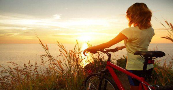 фотография блога леди, идущей на велосипеде по океану во время заката