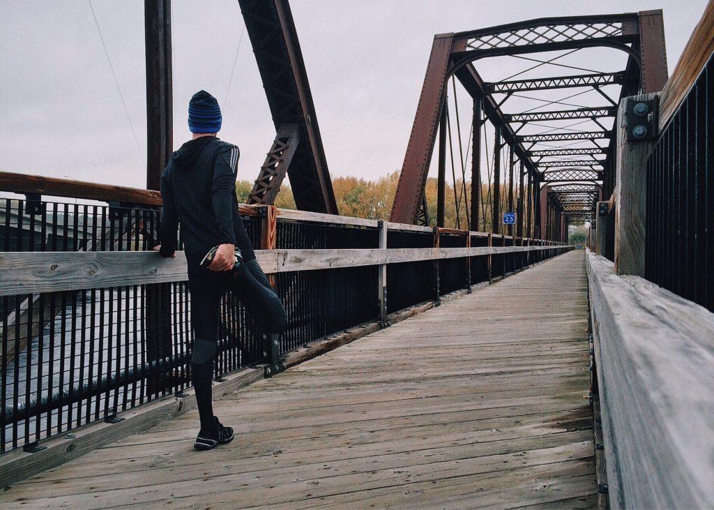 blog de imágenes de un hombre extiende la pierna antes de correr por un puente