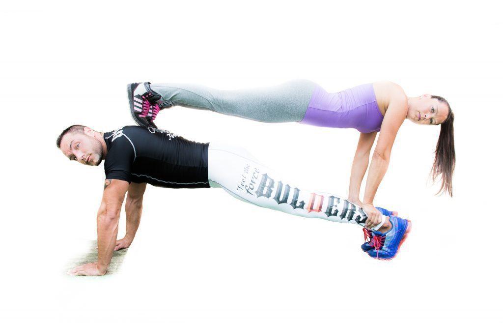 blog de imágenes de un hombre haciendo flexiones y mujer haciendo flexiones en la parte superior de él que enfrenta la otra dirección