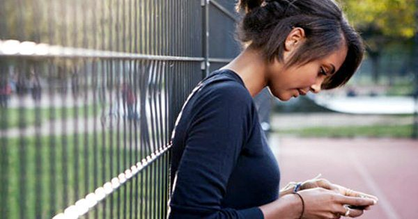 blog picture of teenage girl texting leaning up against a fence
