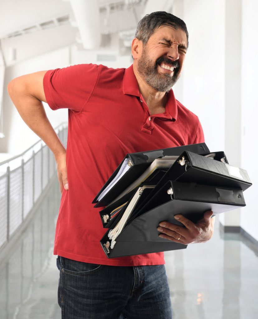 stock photo hispanic businessman experiencing back pain while carrying binders