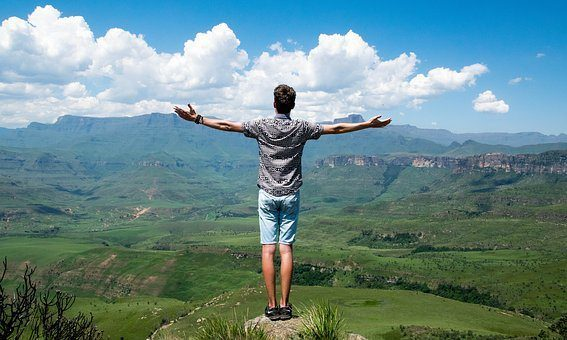 blog picture of a man standing on a hill over looking the country side