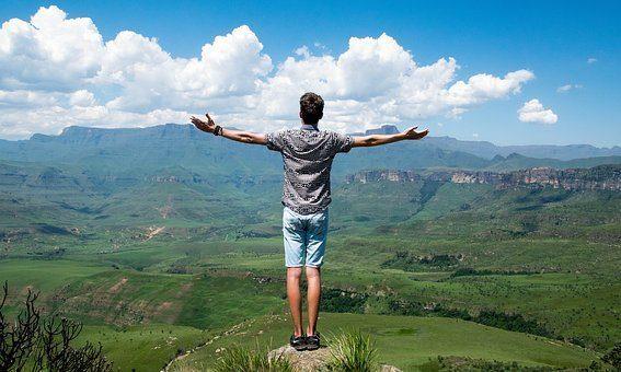 blog di un uomo in piedi su una collina che guarda il paese