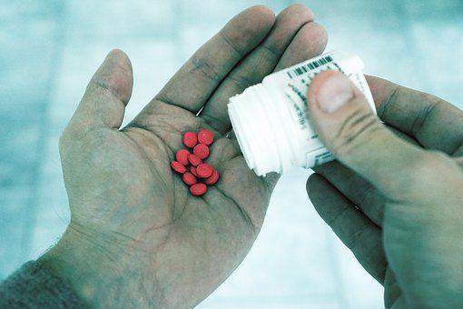 immagine del blog di mano aperta versando alcune pillole in esso