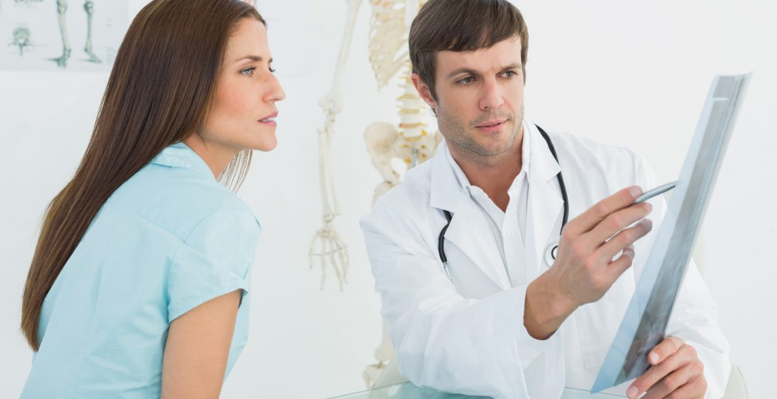 male doctor explaining ray to female patient