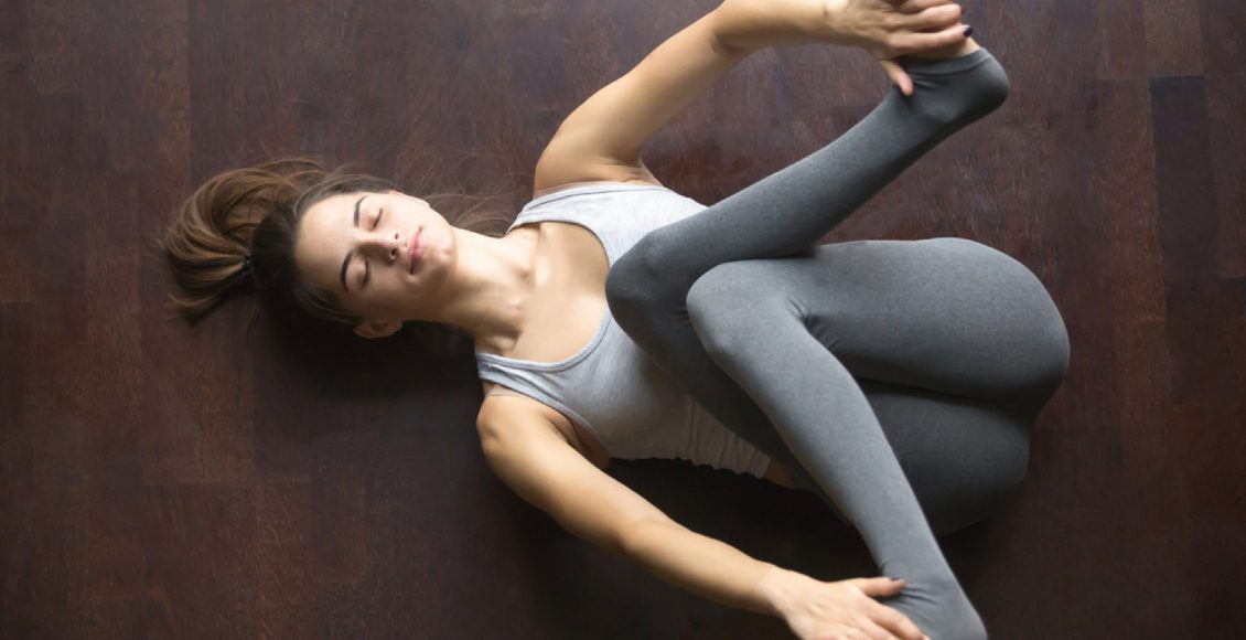 young model working out at home doing yoga exercise on floor lying in supta