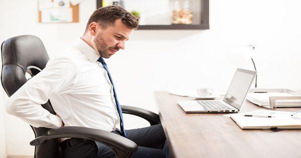 Vyras biuro kėdėje su nugaros skausmais