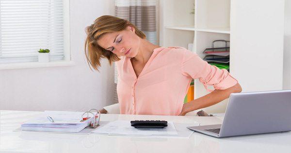 леди на столе с болями в спине от неправильной осанки