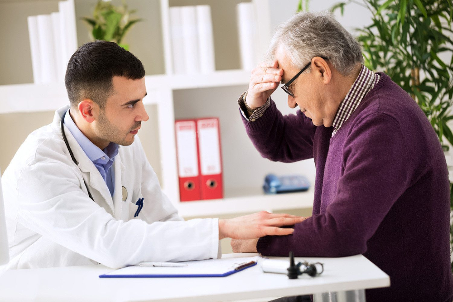 doctor listens to patient explaining headache