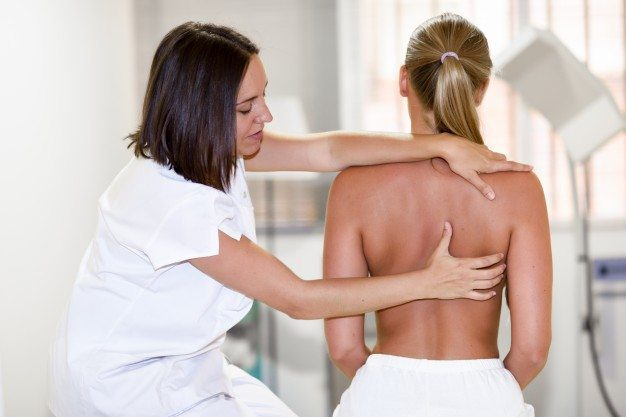 female chiropractor works on patients spine