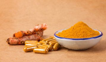 the-turmeric-powder-capsule-and-roots-curcumin-on-wooden-plate