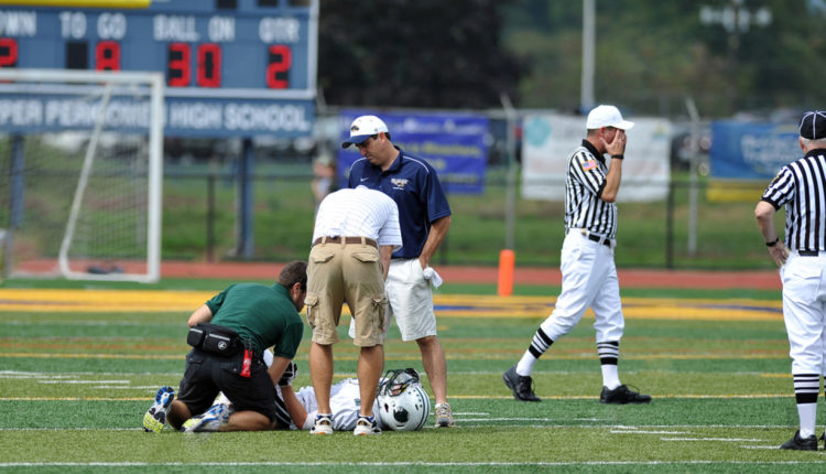 sport injuries high school football player down coaches check him out
