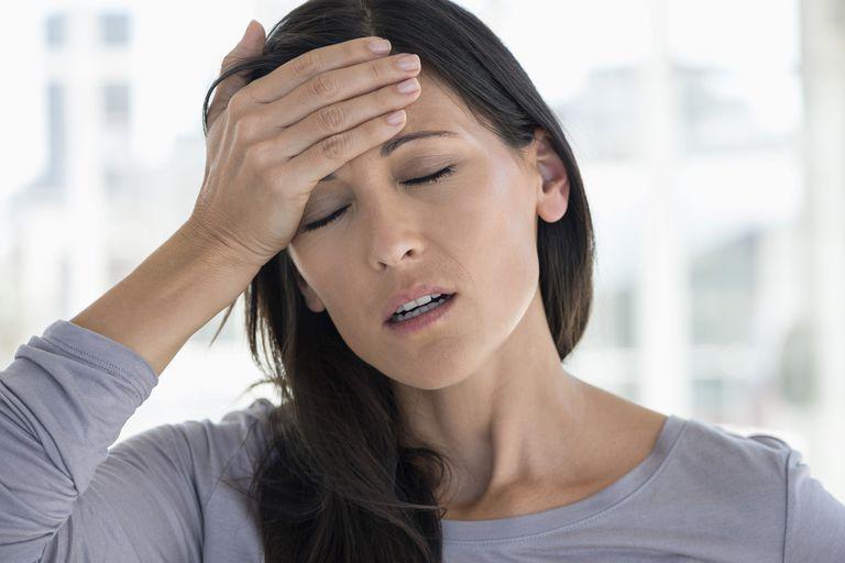 Gambar seorang wanita dengan migrain memegangi kepalanya.