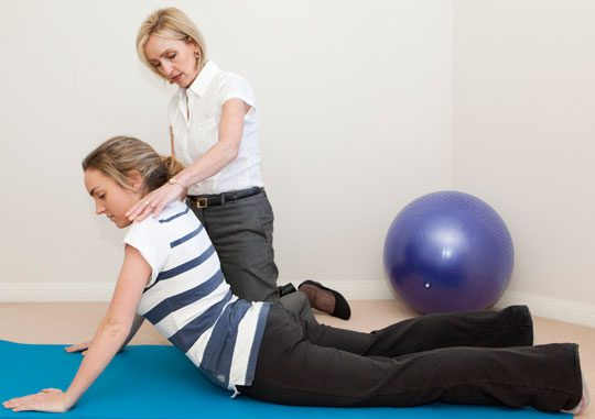 Image of an Instructor demonstrating a patient the McKenzie method | El Paso, TX Chiropractor