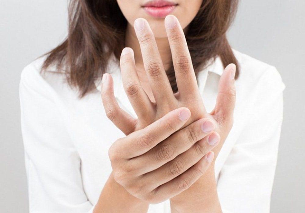 La mujer masajes su mano para aliviar el dolor de la mano.